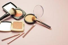 L'ensemble de cosmétiques colorés saupoudrent le correcteur Brushes de fard à joues sur le fond rose Configuration d'appartement  Images stock
