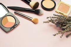 L'ensemble de cosmétiques colorés saupoudrent le correcteur Brushes de fard à joues sur le fond rose Configuration d'appartement  Photographie stock