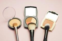 L'ensemble de cosmétiques colorés saupoudrent le correcteur Brushes de fard à joues sur le fond rose Configuration d'appartement  Photos stock