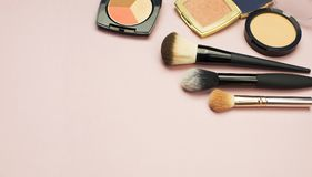 L'ensemble de cosmétiques colorés saupoudrent le correcteur Brushes de fard à joues sur le fond rose Configuration d'appartement  Photo libre de droits
