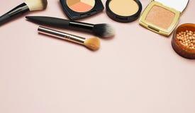 L'ensemble de cosmétiques colorés saupoudrent le correcteur Brushes de fard à joues sur le fond rose Configuration d'appartement  Image libre de droits