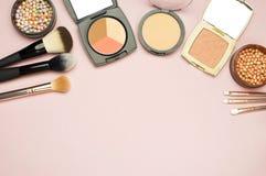 L'ensemble de cosmétiques colorés saupoudrent le correcteur Brushes de fard à joues sur le fond rose Configuration d'appartement  Photos libres de droits
