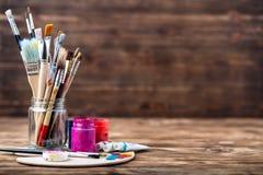 L'ensemble de différentes brosses et de peintures acryliques à peindre a dispersé sur une table en bois foncée Fond de lieu de tr Images stock