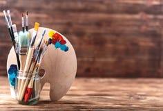 L'ensemble de différentes brosses et de peintures acryliques à peindre a dispersé sur une table en bois foncée Fond de lieu de tr photo libre de droits