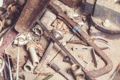 L'ensemble de divers vieil équipement, les instruments rouillés et les outils pour le charpentier travaillent à la table en bois  Image stock