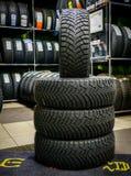 L'ensemble de nouvel hiver fatigue avec les goujons, boutique de pneu à l'arrière-plan images stock