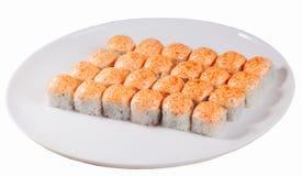 L'ensemble de petits pains de sushi cuits au four d'un plat ovale a isolé le fond blanc, chapeau orange de chapeau de calotte photos stock