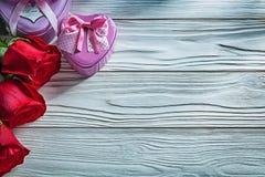 L'ensemble de présent en forme de coeur en métal enferme dans une boîte les roses rouges sur le verrat en bois Photo libre de droits