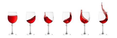 L'ensemble de verres de vin avec éclabousse du vin d'isolement sur le dos de blanc Photos libres de droits