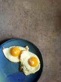 L'ensoleillé-side frit vers le haut des oeufs a tiré le dessus vers le bas du plat bleu Photos stock