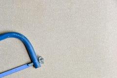 L'entaille bleue de main a vu l'outil pour la coupe en métal photos libres de droits