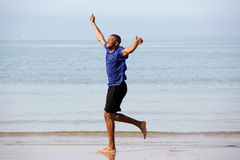 L'ente completo ha eccitato il funzionamento africano del tipo sulla spiaggia con le armi alzate immagine stock libera da diritti