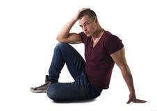 L'ente completo ha sparato del giovane bello che si siede sul pavimento Fotografie Stock