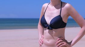 L'ente esile della donna in bikini alla spiaggia della sabbia di mare sta il sunbath viaggia vacanza stock footage