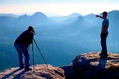 L'enthousiaste de guide touristique et de photo restent avec le trépied sur la falaise et la pensée Paysage rêveur de vieille gal Image libre de droits