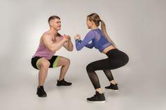 L'entraîneur attirant de forme physique montre à la belle fille comment faire des sguats image libre de droits