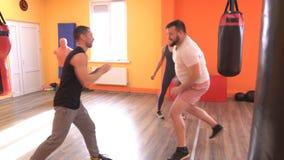 L'entraîneur d'un homme apprend à développer la vitesse et la réaction en arts martiaux de son élève un homme barbu, forme physiq banque de vidéos