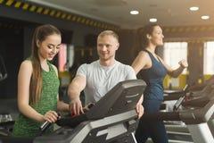 L'entraîneur de forme physique aide la femme sur l'entraîneur elliptique images stock