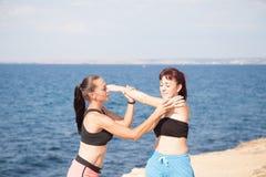 L'entraîneur de forme physique de fille montre des sports d'exercices sur la plage Photo libre de droits