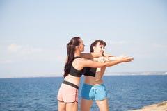 L'entraîneur de forme physique de fille montre des sports d'exercices sur la plage Photographie stock libre de droits