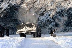 L'entraîneur de nettoyage de neige efface des chemins Photographie stock libre de droits