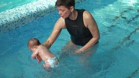 L'entraîneur enseignent le bébé à plonger banque de vidéos