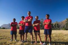 L'entraîneur et les enfants se tenant avec des bras ont croisé dans le camp de botte Photos libres de droits
