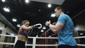 L'entraîneur explique la technique de poinçon au boxeur de femme sur des premiers rangs clips vidéos