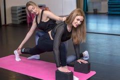 L'entraîneur féminin aide une femme à faire des exercices images libres de droits
