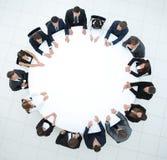 L'entraîneur mène la session avec l'équipe d'affaires s'asseyant à une table ronde Photographie stock libre de droits