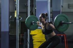 L'entraîneur musculaire attirant puissant de CrossFit de femme font la séance d'entraînement avec le barbell images stock