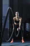 L'entraîneur musculaire attirant puissant de CrossFit luttent la séance d'entraînement avec des cordes photographie stock