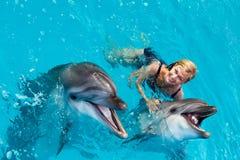 L'entraîneur nage dans l'eau avec des dauphins Photos stock