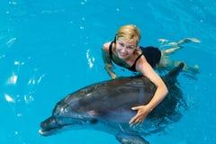 L'entraîneur nage dans l'eau avec des dauphins Photo stock