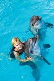 L'entraîneur nage dans l'eau avec des dauphins Image libre de droits