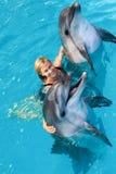 L'entraîneur nage dans l'eau avec des dauphins Photo libre de droits