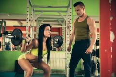 L'entraîneur personnel de forme physique forme la belle femme dans le gymnase photos libres de droits