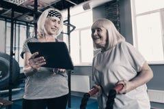 L'entraîneur personnel féminin montrant la bataille ropes le cours de séance d'entraînement Photos libres de droits