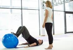 L'entraîneur personnel montre l'exercice avec la boule Photographie stock