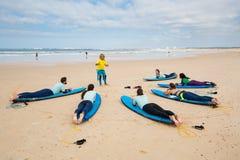 L'entraîneur surfant instruit des surfers de novice près de Peniche Images stock