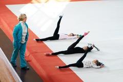 L'entraîneur surveille la conformité étirant des exercices pour des jambes photos libres de droits