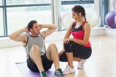 L'entraîneur féminin regardant l'homme font des craquements abdominaux Image stock