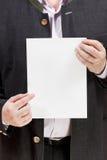 L'entraîneur tient la page du papier blanche dans des mains Photos stock