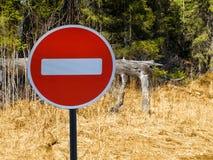 L'entrata del segno è proibita contro lo sfondo della foresta e dell'erba asciutta fotografia stock libera da diritti