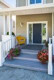L'entrata principale della casa della famiglia con la sedia gialla nell'ambito del portico e dello sbocciare decorativo fiorisce immagine stock libera da diritti