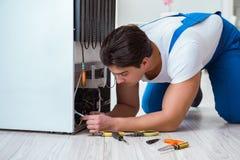 L'entrepreneur de dépanneur réparant le réfrigérateur dans le concept diy Image libre de droits