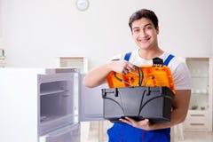 L'entrepreneur de dépanneur réparant le réfrigérateur dans le concept diy Photo stock