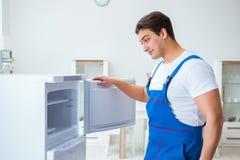 L'entrepreneur de dépanneur réparant le réfrigérateur dans le concept diy Photos libres de droits