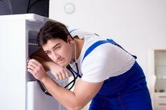 L'entrepreneur de dépanneur réparant le réfrigérateur dans le concept diy Photo libre de droits