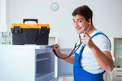 L'entrepreneur de dépanneur réparant le réfrigérateur dans le concept diy Photographie stock libre de droits